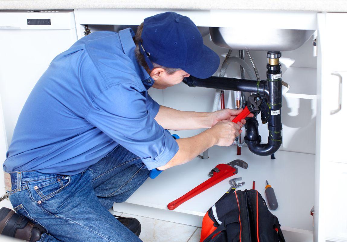 Hydraulik w kuchni naprawiający zlew Szczecin